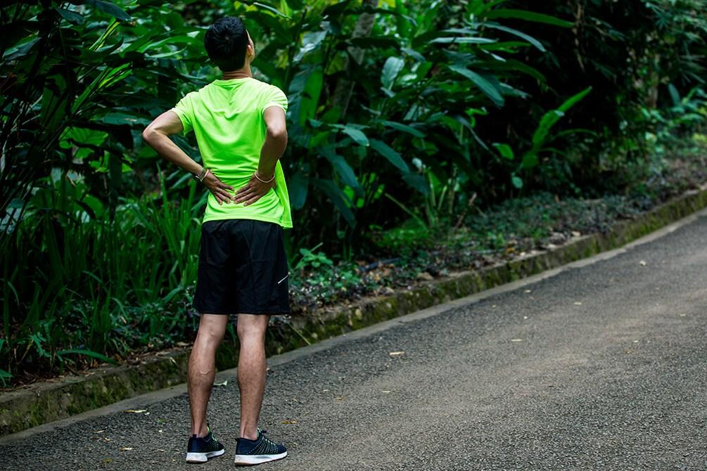 Corredor parado em pista de brita com as mãos nas costas, indicando dor na lombar