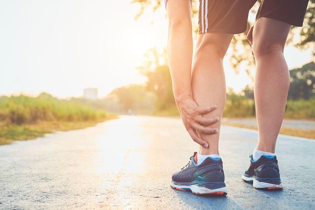 um homem parado na pista de corrida com a mão na perna esquerda indicando dor no tornozelo