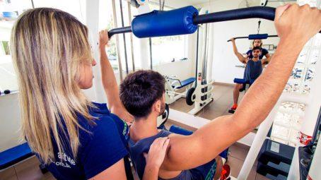 Professora auxilia aluno no exercício em aparelho de musculação