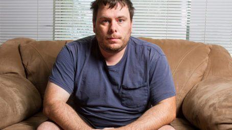 um homem acima do peso sentado no sofá